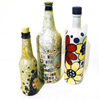 Bottles covered with book pages, maps, and paint.